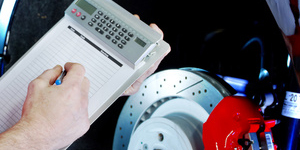 Car mechanic makes a calculation of repair costs for a brake